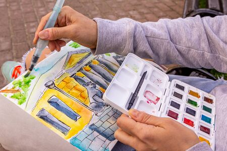 girl draws a picture with watercolor paints, close up. drawing on the open air. Banco de Imagens