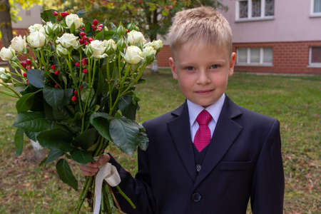 Portrait of a blond boy dressed in a classic suit and holding a bouquet of roses, looking to camera. First grader going to go to school.
