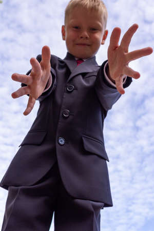 Portrait of a blond first-grader boy dressed in a dark suit with his arms outstretched to the camera on background of cloudy sky. A boy having fun, blur and grain effect.