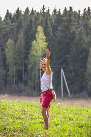 A young long haired woman having fun on the field on background of forest.