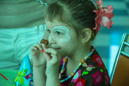 04/29/2012, Maloyaroslavets, Russia. portrait of a little girl with face painting, side view.