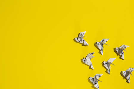 Flock of flying origami doves on yellow background. Origami bird's group from music paper. Concept of festive music postcard.