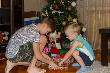 31.12.2018, Maloyaroslavets, Russia. two boys unfold their gifts in the early morning. festive mood concept. 報道画像