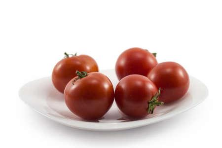 Five ripe tomato on a white plate photo