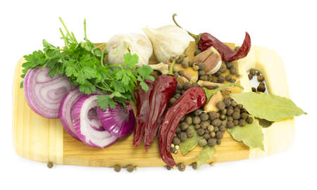 spices, bay leaf, pepper, hot pepper, onion and garlic on cutting board Stock Photo