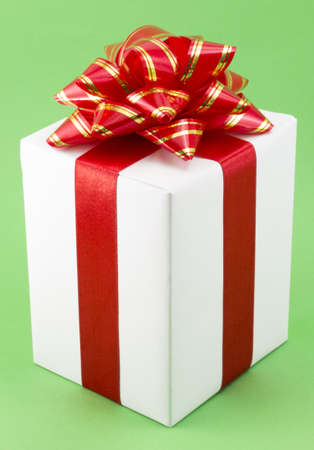White Gift Box with Red Ribbon Bow on green background photo