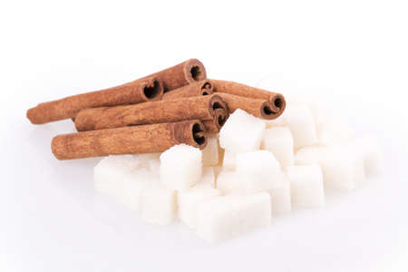 cubes of sugar and cinnamon isolated on white background photo