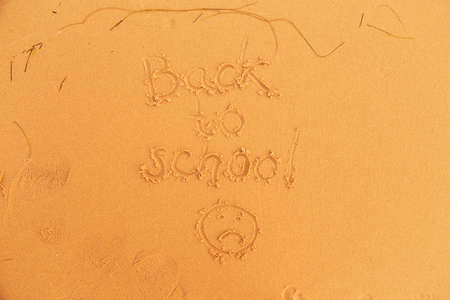 green face: back to school inscription sand