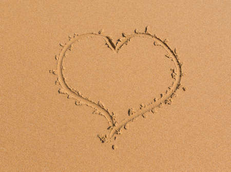 heart drawn in the sand on the beach photo