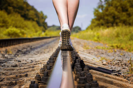 female legs in sneakers on the rail of the railway photo