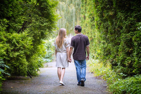 couple walk holding hands park photo