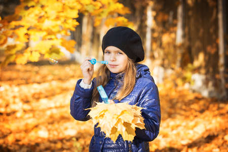 blowing bubbles: young girl blowing bubbles autumn park Stock Photo