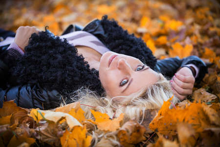 blonde woman lying in the autumn park photo