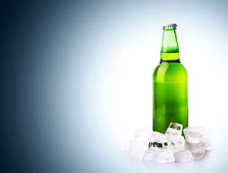 beer bottle in ice cubes on blue background photo