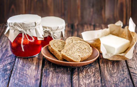 bread and butter: bread butter strawberry jam on a wooden background