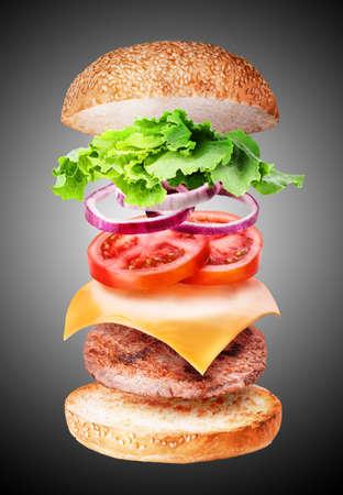 gravedad: Volando ingredientes de hamburguesa en un fondo negro