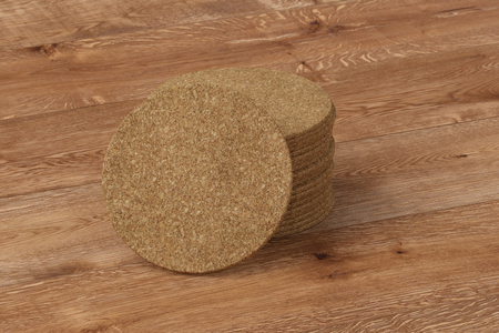 corkwood: Beer coaster. Isolated on wooden table. Include clipping path. 3d render