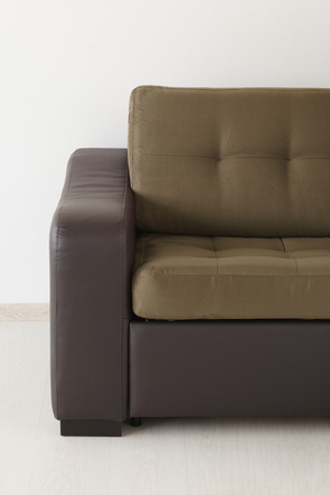 Brown leather sofa isolated against the wall