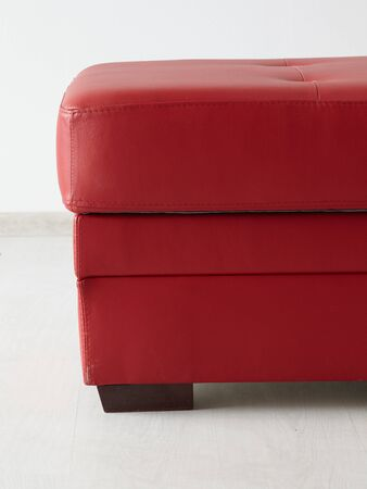 Red leather stool isolated isolated against the wall