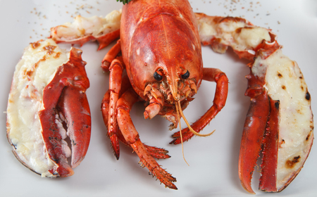 Boiled lobster. A dish with omar of  european cuisine. White plate on a brown wooden table. Close up side view.