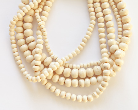 Jewelry necklace made of threads with bone beads  on white background. Many strands of varying sized beads of polished ivory