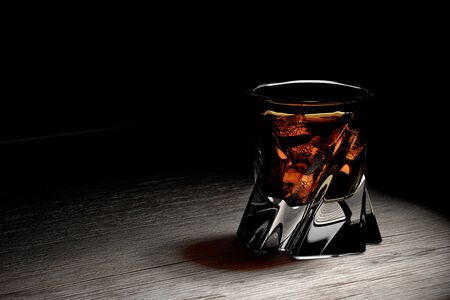 bourbon whisky: Scotch on wooden background with copy-space. An old and vintage countertop with highlight and a glass of hard liquor. 3D render