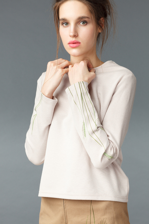 Portrait of young elegant woman with beautiful hands on white pullover or sweater with green embroidery. Closeup Stock Photo