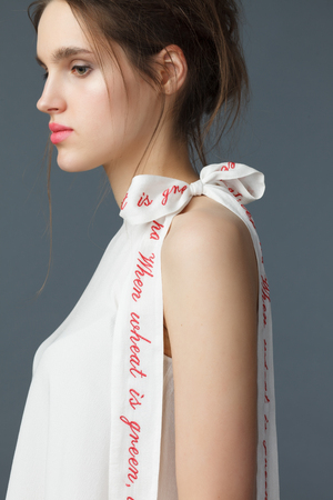 Portrait of beautiful young woman dressed in a elegant white silk tunic with a drawstring ribbon with calligraphic embroidery