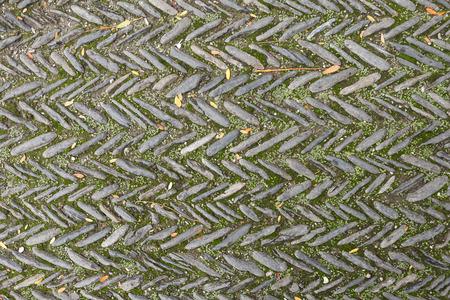 De textuur van de oude visgraatbestrating van keien met mos tussen de stenen in de kloosterbinnenplaats in Spanje. Bekijk hierboven Stockfoto