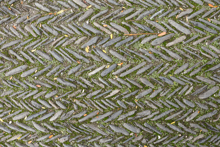 The texture of the old herringbone pavement of cobblestones with moss between the stones in the monastery courtyard in Spain. View above Banco de Imagens