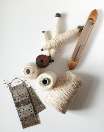 Still life in a textile manufactory. Spools of thread, sketches, textile patterns, shuttles