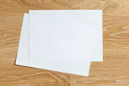 Two of blank sheets of paper landscape orientation on wooden background