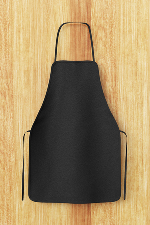 Blank black apron isolated on wooden background with clipping path. 3d illustration.