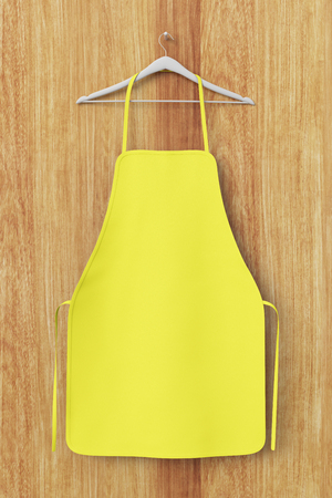 Blank yellow apron isolated on wooden background with clipping path. 3d illustration.