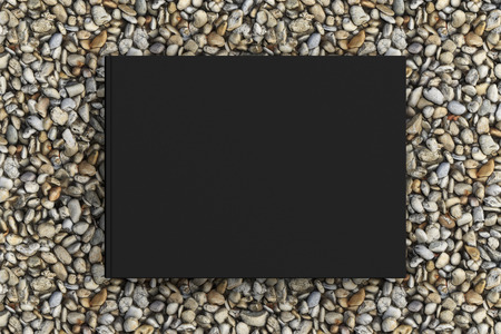 Blank landscape black book cover mockup on gravel isolated with clipping path around cover. 3d illustration