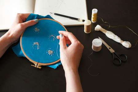 Workplace embroiderers: outline in a notepad, embroidery hoop, scissors and thread. Hands of the master