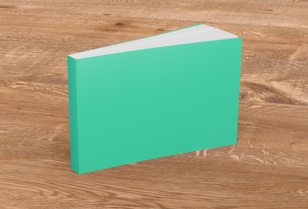 Blank turquoise horizontal soft cover book standing on wooden background. Isolated with clipping path around book. 3d illustration