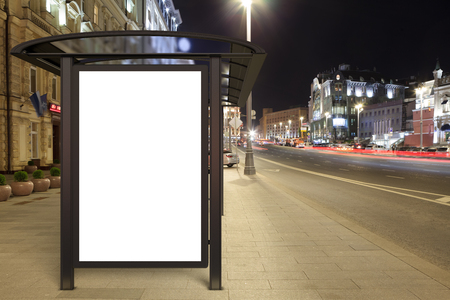 Blank advertising billboard on bus stop at night with street city lights. 3D illustration