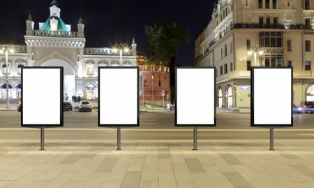 city background: Four blank street billboards at night.