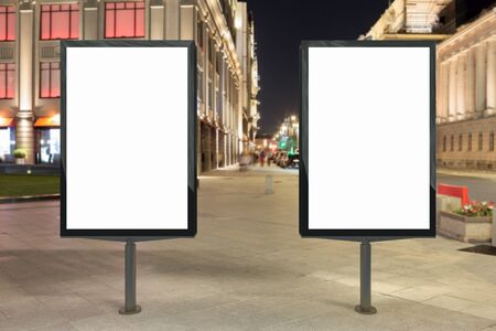 Two blank street billboards at night. Isolated with clipping path around advertising display. 3d illustration.