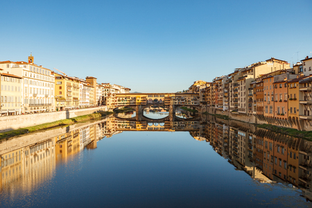 View of bridge Ponte Vecchio and the Arno River from the Ponte Santa Trinita in Florence, Tuscany, Italy.