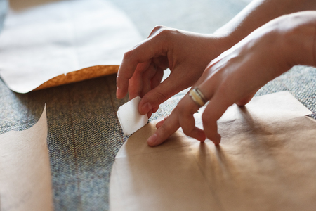 Atelier design studio on tailoring.  The woman draws with soap markup patterns on tweed fabric. Close up view. Stock Photo