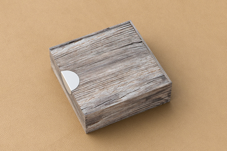Blank vintage wooden square box with closed sliding lid on beige leather background. Include clipping path around box. 3d illustration