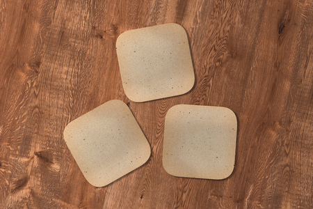 Three square vintage coasters on wood background. 3d illustration