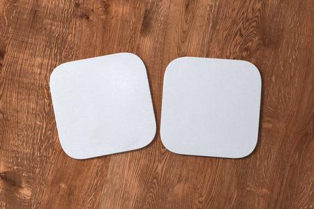 Twee vierkante witte onderzetters op houten achtergrond. 3D illustratie Stockfoto