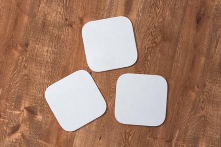Drie vierkante witte onderzetters op houten achtergrond. 3D illustratie Stockfoto