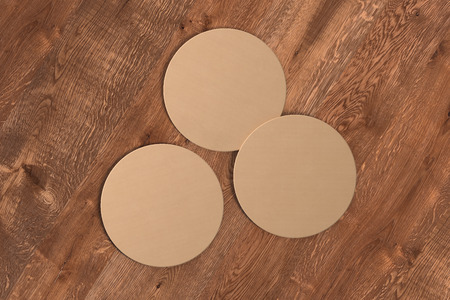 Three round craft paper coasters on wood background. 3d illustration