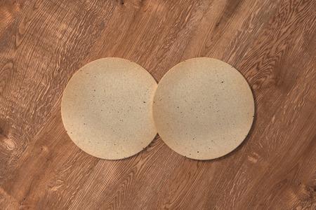 Twee ronde uitstekende onderzetters op houten achtergrond. 3D illustratie
