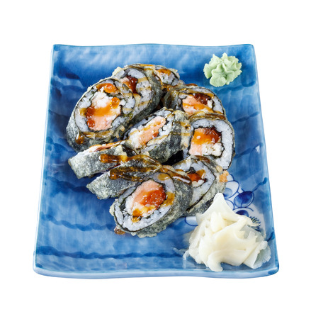 Sushi rolls on a plate with salmon and cucumber on wooden table. Isolated with clipping path