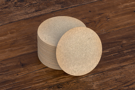 Vintage round beer coasters on wooden background  around coasters. 3d illustration